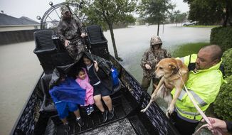 Richard Velasco lifts his dog into an airboat as he and his family are evacuated from their home as water rises from heavy rains from Tropical Storm Harvey on Monday, Aug. 28, 2017, in Fort Bend County, Texas. (Brett Coomer/Houston Chronicle via AP)