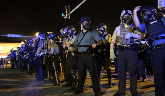In this file photo taken Aug. 18, 2014, police are in riot gear work to disperse a crowd of protesters in Ferguson, Mo. (AP Photo/Jeff Roberson)