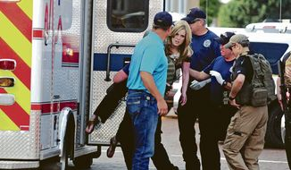 An injured woman is carried to an ambulance in Clovis, N.M., Monday, Aug. 28, 2017, as authorities respond to reports of a shooting inside a public library. A city official says police have taken a person into custody who they believe is responsible for a shooting at the library. (Tony Bullocks/The Eastern New Mexico News via AP)