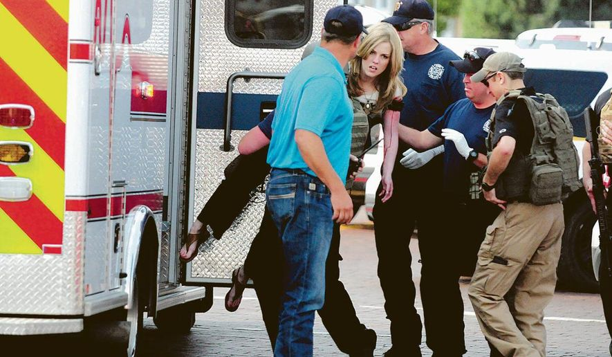 A shooting victim at Clovis-Carver Public Library in New Mexico is helped into an ambulance on Monday. (Photograph by The Eastern New Mexico News)