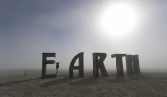FILE - In this Saturday Aug. 27, 2016, file photo, Anita Vranckx, of Belgium, hangs from the E of an Earth sculpture at Burning Man on a dusty morning on the playa in the Black Rock Desert near Gerlach, Nev. Tens of thousands have braved massive traffic jams to get to the remote stretch of Nevada desert for the 2017 Burning Man festival that runs until Sept. 4, 2017. (Andy Barron/The Reno Gazette-Journal via AP, File)