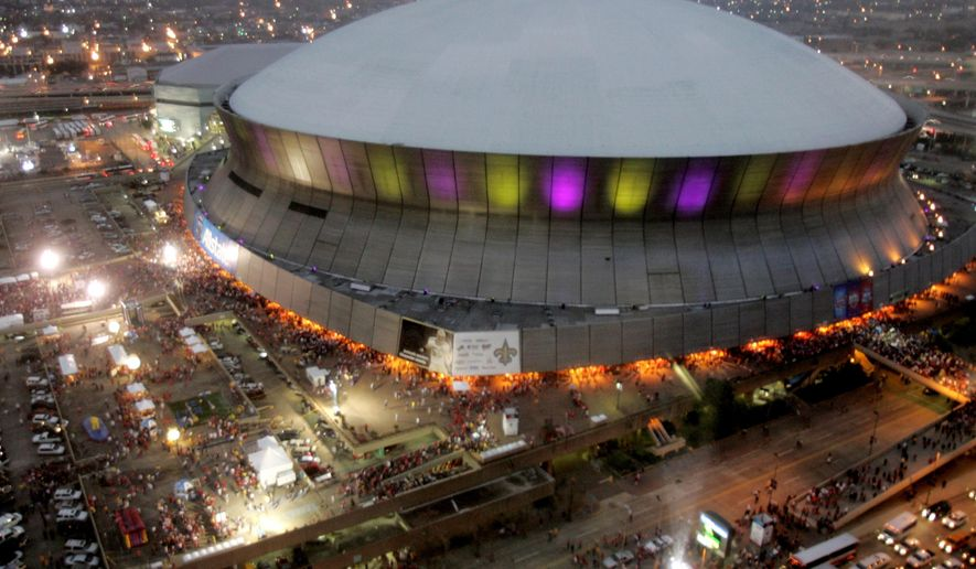 FILE - In this Jan. 7, 2008, file photo, color lights play on the Louisiana Superdome at twilight before the BCS championship college football game in New Orleans. The BYU-LSU game will be played Saturday, Sept. 2, 2017 at the Superdome in New Orleans after massive flooding in Houston from Hurricane Harvey forced it to be relocated from NRG Stadium. (AP Photo/Rob Carr, File)