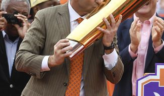 FILE - In this Jan. 14, 2017, file photo, Clemson head coach Dabo Swinney kisses the National Championship Trophy during a celebration at Memorial Stadium honoring the NCAA college football champions, in Clemson, S.C. Swinney has spent months drilling the good feelings of a national title out of the fifth-ranked Tigers heading into the season. This group starts making its own title run Saturday against Kent State. (Bart Boatwright/The Greenville News via AP, File)