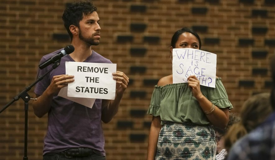 In this Sunday, Aug. 27, 2017 photo, two community members hold up signs as they speak to a crowd in the Martin Luther King Jr. Performing Arts Center during a community meeting organized by the Department of Justice's Community Relations Service in Charlottesville, Va. Charlottesville residents told city leaders at an emotional community meeting they were traumatized by a white nationalist rally and dissatisfied with the way officials handled the event and the violence that unfolded. (Zack Wajsgras/The Daily Progress via AP)
