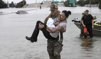 Houston Police SWAT officer Daryl Hudeck carries Catherine Pham and her 13-month-old son Aiden after rescuing them from their home surrounded by floodwaters from Tropical Storm Harvey Sunday, Aug. 27, 2017, in Houston. The remnants of Hurricane Harvey sent devastating floods pouring into Houston Sunday as rising water chased thousands of people to rooftops or higher ground. (AP Photo/David J. Phillip)