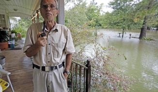 Jimmie Bradley speaks about the flooding in his neighborhood in Moss Bluff, a Lake Charles, La., suburb in Calcasieu Parish, Monday, Aug. 28, 2017. Bradley, 78, and his wife Brenda, had stacked sandbags at their doors, but the rising water was lapping at the steps to their back porch and had overtaken their front yard. Virtually every neighbor on Crawford Drive has at least a foot of water in their yards. (AP Photo/Rogelio V. Solis)