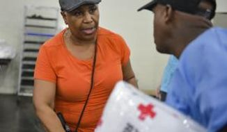Margaret Ryan volunteers at the George R. Brown Convention Center in Houston serving food to evacuees from Hurricane Harvey, Monday, Aug. 28, 2017.  (Scott Clause/The Daily Advertiser via AP)