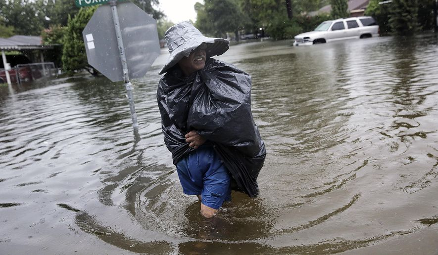A Melrose Place neighbor wears makeshift rain gear as he walks the flooded streets to check on his Houston neighbors as Tropical Storm Harvey makes its way through the area on Monday, Aug. 28, 2017. (Elizabeth Conley/Houston Chronicle via AP)