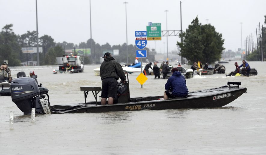 Volunteer rescue boats make their way into a flooded subdivision to rescue stranded residents as floodwaters from Tropical Storm Harvey rise Monday, Aug. 28, 2017, in Spring, Texas. (AP Photo/David J. Phillip)