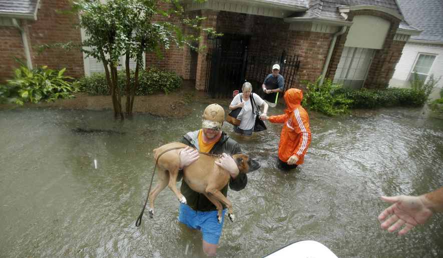 Volunteers evacuate a neighborhood inundated by floodwaters from Tropical Storm Harvey on Monday, Aug. 28, 2017, in Houston, Texas. (AP Photo/Charlie Riedel)