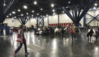 People seek shelter from the aftermath of Hurricane Harvey at the George R. Brown Convention Center in Houston on Sunday, Aug. 27, 2017. Rising floodwaters from the remnants of Hurricane Harvey chased thousands of people to rooftops or higher ground Sunday in Houston, overwhelming rescuers who fielded countless desperate calls for help. (Elizabeth Conley/Houston Chronicle via AP)