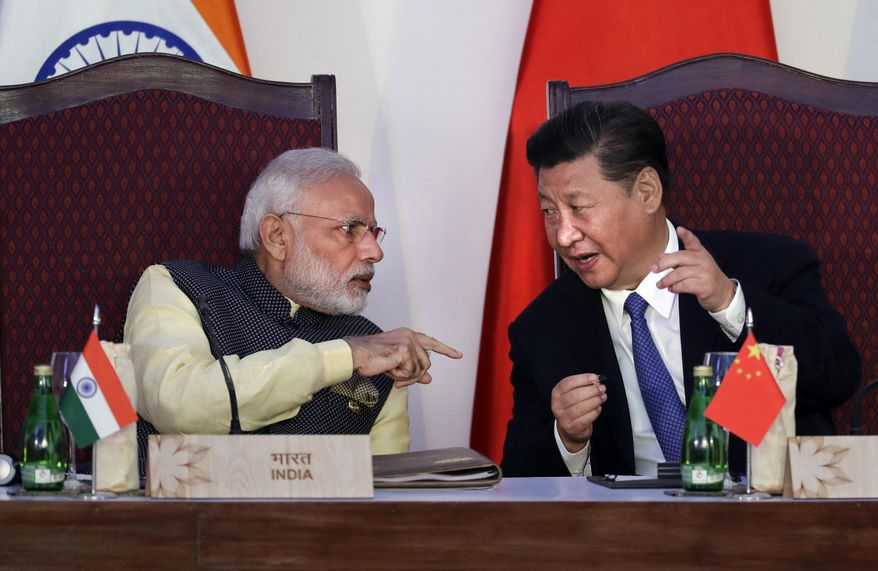 In this Oct. 16, 2016, file photo, Indian Prime Minister Narendra Modi, left, talks with Chinese President Xi Jinping at the BRICS summit in Goa, India. India and China have agreed to pull back their troops from a face-off in the high Himalayas where China, India and Bhutan meet, signaling a thaw in the monthslong standoff, India's government said Monday, Aug. 28, 2017. (AP Photo/Manish Swarup, File)