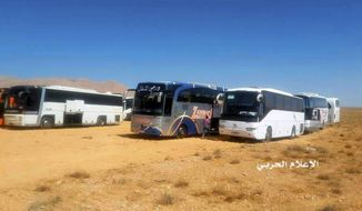 This photo provided on Monday, Aug 28, 2017 by the government-controlled Syrian Central Military Media, shows buses gathering before a planned evacuation of Islamic State group militants, in the mountainous region of Qalamoun, Syria. The remains of eight Lebanese soldiers kidnapped by the Islamic State group three years ago were located Sunday, a senior Lebanese official said, in a negotiated deal that followed a military offensive to drive the militants out of the border area with Syria. (Syrian Central Military Media, via AP)