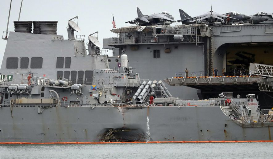 FILE - In this Aug. 22, 2017 file photo, the damaged port aft hull of USS John S. McCain, left, is seen while docked next to USS America at Singapore's Changi naval base in Singapore. The collision between the USS John S. McCain and an oil tanker highlighted a long-simmering dispute between Singapore and Malaysia over which country should control a 60-meter (197-foot) wide guano-encrusted outcropping at the edge of the South China Sea. (AP Photo/Wong Maye-E, File)