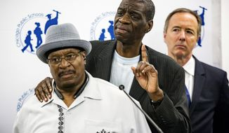 Anthony Holmes, left, and Darrell Cannon, victims of torture by the former Police Commander Jon Burge, speak at a news conference in Chicago, Monday, Aug. 28, 2017, where it was announced that Chicago Public Schools students will be taught about the police torture scandal that has dogged the city and the police department. Monday's announcement comes more than two years after the City Council approved an ordinance that called for the city to pay $5.5 million in reparations to the African-American victims of torture at the hands of Burge and his detectives. Listening at right is Chicago Public Schools CEO Forrest Claypool. (James Foster/Chicago Sun-Times via AP)