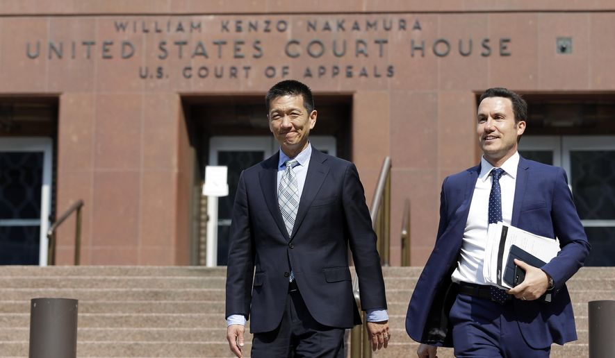 Hawaii Attorney General Doug Chin, left, smiles as he leaves a federal courthouse with assistant Joshua Wisch after appearing there Monday, Aug. 28, 2017, in Seattle. The fight over President Donald Trump's travel ban returned to the 9th U.S. Circuit Court of Appeals Monday, with the government seeking to overturn a lower court order that makes it easier for travelers from six mostly Muslim countries to enter the United States. (AP Photo/Elaine Thompson)