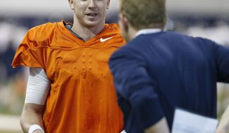 FILE - In this Thursday, April 6, 2017, file photo, Virginia quarterback Kurt Benkert talks with quarterback coach, Jason Beck, right, during a spring football practice at their indoor facility in Charlottesville, Va. This year, Benkert's ability to stay healthy will likely go a long way in determining their ability to improve on their 2-10 record of last year. (AP Photo/Steve Helber)