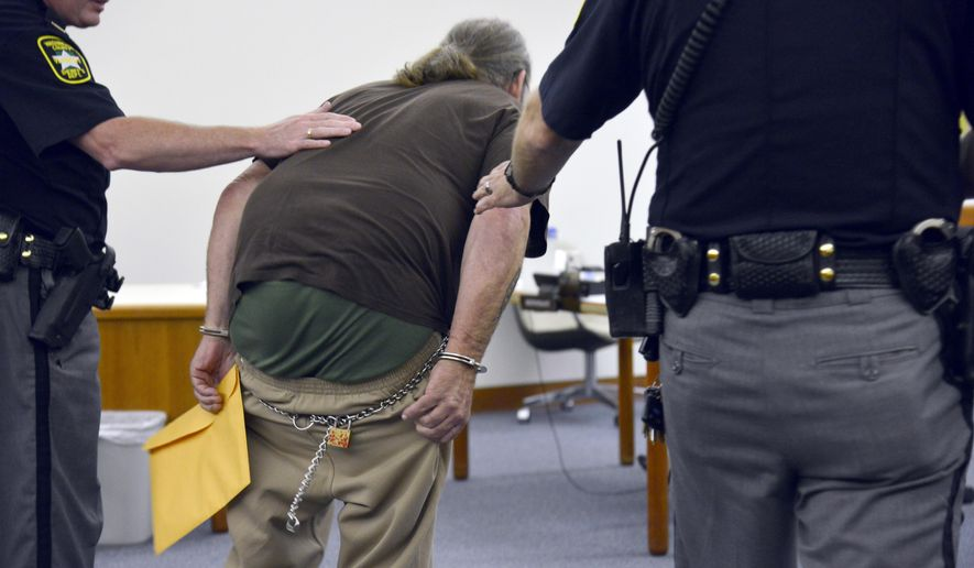 Randal Gibo bends over and pulls his pants down in front of news crews while being escorted into the courtroom Monday, Aug. 28, 2017, in Barre, Vt., for his arraignment on a murder charge for the death of his late girlfriend, Cindy Cook, 59 of Barre, whose bound body was found July 12 near a brook in Middlesex. Gibo pleaded not guilty to first-degree murder charges. (Stefan Hard/The Times Argus via AP, Pool)