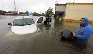 Conception Casa, center, and his friend Jose Martinez, right, check on Rhonda Worthington after her car became stuck in rising floodwaters from Tropical Storm Harvey in Houston, Texas, Monday, Aug. 28, 2017. The two men were evacuating their home that had become flooded when they encountered Worthington's car floating off the road. (AP Photo/LM Otero)
