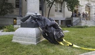 In this Aug. 14, 2017, file photo, a toppled Confederate statue lies on the ground on Monday, Aug. 14, 2017, in Durham, N.C. Three more people have been charged with toppling the Confederate statue earlier this month. Durham County jail records show that Jessica Nicole Jude, Joseph Baldoni Karlik and Qasima Rohan Elise Wideman were arrested Monday, Aug. 28, and later released. (Virginia Bridges/The Herald-Sun via AP, File)