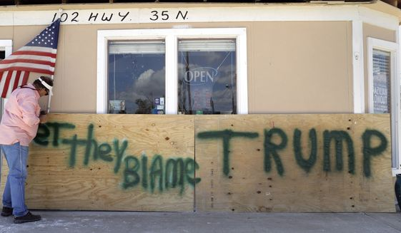 """John Murray attached an American flag to a sign reading """"Bet They Blame Trump"""" at his hurricane-damaged business on Tuesday before the president made his visit to the state. (Associated Press)"""