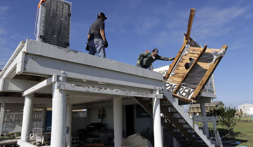 Felix Tijerina, right, and Andy Guerra, left, try to salvage items from their family home that was destroyed in the wake of Hurricane Harvey, Tuesday, Aug. 29, 2017, in Rockport, Texas. (AP Photo/Eric Gay)