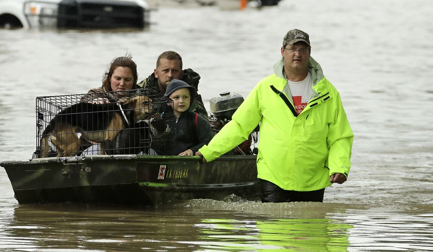 People evacuate a neighborhood in west Houston inundated by floodwaters after a release from nearby Addicks Reservoir when it reached capacity Tuesday. (Associated Press)