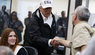President Donald Trump is greeted as he tours the Texas Department of Public Safety Emergency Operations Center, Tuesday, Aug. 29, 2017, in Austin, Texas. (AP Photo/Evan Vucci)