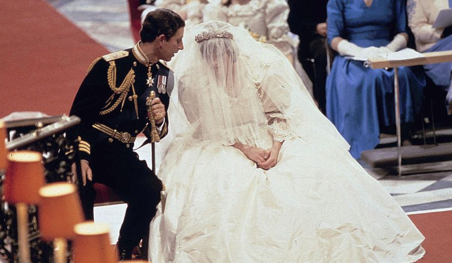 FILE - In this file photo dated July 29 1981, Britain's Prince Charles as he speaks with his bride Princess Diana, during their wedding ceremony in St. Paul's Cathedral, London. Of its time, but Lady Diana Spencer's fairytale wedding dress in 1981 delighted royal fans with its full silk taffeta gown and 25ft train by designers David and Elizabeth Emanuel. (AP Photo/File)