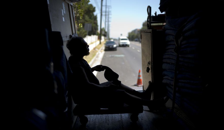 Moving company employee Oscar Vaquez, 29, takes off his hat while resting in a freight container Tuesday, Aug. 29, 2017, in Los Angeles. California energy authorities urged voluntary conservation of electricity Tuesday as a wave of triple-digit heat strained the state's power grid. (AP Photo/Jae C. Hong)