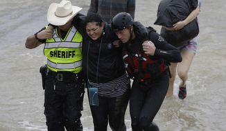 A woman is helped by rescue personnel while being evacuated as floodwaters from Tropical Storm Harvey rise Monday, Aug. 28, 2017, in Houston. (AP Photo/David J. Phillip)