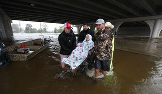 Volunteers and Harris County Sheriff deputies lift an elderly person on a wheelchair over the flooded C.E. King Parkway under the East Sam Houston North on Monday, Aug. 28, 2017, in Houston. (Steve Gonzales/Houston Chronicle via AP)