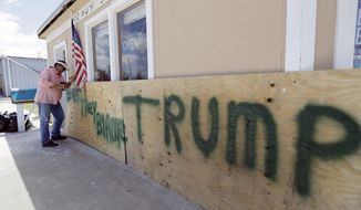 """John Murray attaches a U.S. flag to a sign reading """"Bet They Blame Trump"""" at his business damaged in the wake of Harvey, Tuesday, Aug. 29, 2017, in Rockport, Texas. Murray created the sign in hopes President Donald Trump would visit Rockport during his Texas visit, but he did not expect him to make the trip. AP Photo/Eric Gay)"""
