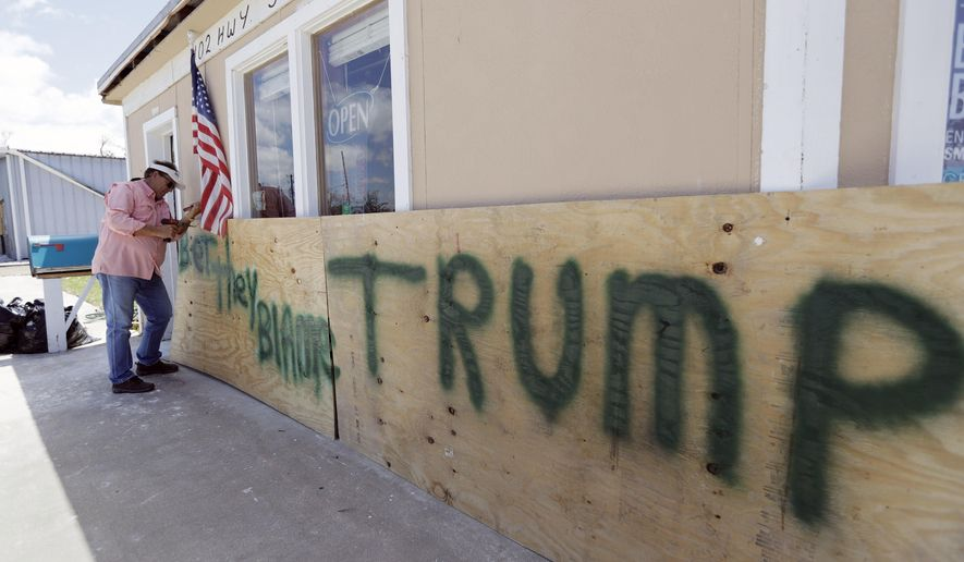 "John Murray attaches a U.S. flag to a sign reading ""Bet They Blame Trump"" at his business damaged in the wake of Harvey, Tuesday, Aug. 29, 2017, in Rockport, Texas. Murray created the sign in hopes President Donald Trump would visit Rockport during his Texas visit, but he did not expect him to make the trip. AP Photo/Eric Gay)"