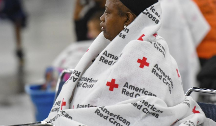 An evacuee rests at the George R. Brown Convention Center in Houston, Monday, Aug. 28, 2017.  Houston was still largely paralyzed Monday, and there was no relief in sight from the storm that spun into Texas as a Category 4 hurricane, then parked itself over the Gulf Coast. (Scott Clause/The Daily Advertiser via AP)