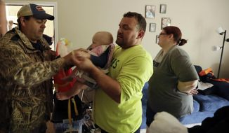 Michael Reznor, center, holds his son while he is fitted for a life vest as he and his family are evacuated from their apartment among floodwaters from Tropical Storm Harvey Tuesday, Aug. 29, 2017, in Kingwood, Texas. Reznor's wife Ashlyn Reznor looks on at right. (AP Photo/Gregory Bull)
