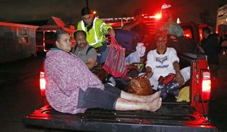 Residents ride in the bed of an emergency vehicle carrying them to safety following flooding to their homes late Monday night, Aug. 28, 2017 in Lake Charles, La. Almost constant rain over the last two days from Harvey, overcame the city's drainage system, flooding several subdivisions and necessitating home rescues. (AP Photo/Rogelio V. Solis)