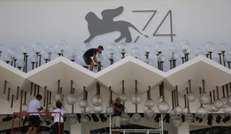 Workers set up lighting at the Cinema Palace ahead of the 74th edition of the Venice Film Festival, at the Venice Lido, Italy, Monday, Aug. 28, 2017. The world's oldest cinema festival, which opens Wednesday, is kicking off the fall cinema season with searing drama, serious glamour and a crop of new movies vying for attention, awards and acclaim. (AP Photo/Domenico Stinellis)