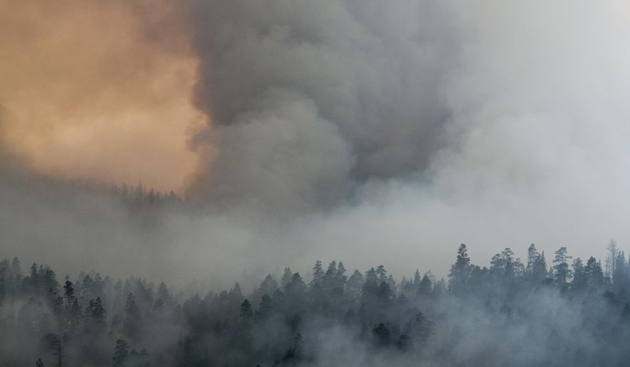 In this Sunday, Aug. 27, 2017, photo, smoke from a wildfire west of Sisters, Ore., blanket the Deschutes National Forest. Firefighters in southern Oregon on Tuesday, Aug. 29, gained a toehold on a fire burning near the coastal town of Brookings but new evacuations were ordered after a flare-up on a different complex of lightning-caused fires in a remote area near the California border. (Fedor Zarkhin/The Oregonian via AP)
