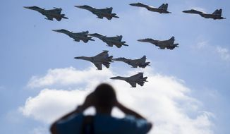 FILE - In this file photo taken on Saturday, Aug. 12, 2017 a man watches Russian military jets performing in Alabino, outside Moscow, Russia. The Russian military says major war games, the Zapad (West) 2017 maneuvers, set for next month will not threaten anyone. (AP Photo/Pavel Golovkin, File)