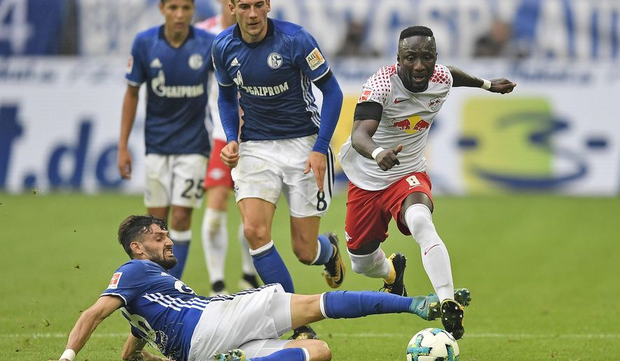 FILE - In this Aug. 19, 2017 file photo Leipzig's Naby Keita, right, and Schalke's Daniel Caligiuri, left, vie for the ball during the German Bundesliga soccer match between FC Schalke 04 and RB Leipzig at the Arena in Gelsenkirchen, Germany. Liverpool has reached an agreement to sign Naby Keita from German club Leipzig, with the Guinea midfielder moving to Anfield at the end of this season. (AP Photo/Martin Meissner)