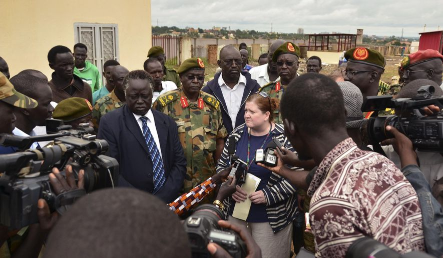 U.S. Consul Denise Knapp, center, speaks to the media, accompanied by South Sudanese army officials and ministry of foreign affairs representatives, after the body of killed American journalist Christopher Allen was officially handed over to the U.S. embassy, at a mortuary in the capital Juba, South Sudan Tuesday, Aug. 29, 2017.  The 28-year-old freelance journalist was killed Saturday amid fighting between government and rebel forces near the Ugandan border. (AP Photo/Mariah Quesada)