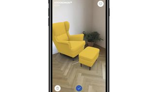 This photo provided by Ikea demonstrates Ikea's augmented reality app called IKEA Place, on an iPhone, allowing a user to superimpose virtual images over real-life settings. The app allows shoppers to see how furniture will look in their living room or other space before buying it. (Ikea via AP)