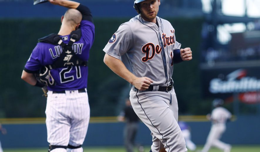 Detroit Tigers' Alex Presley, front, scores from third base on a double hit by Justin Upton as Colorado Rockies catcher Jonathan Lucroy, back, reacts in the first inning of a baseball game, Monday, Aug. 28, 2017, in Denver. (AP Photo/David Zalubowski)