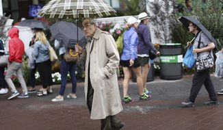 Don Kregsman, center, walks through the grounds of the Billie Jean King National Tennis Center during a rain delay in the first round of the U.S. Open tennis tournament, Tuesday, Aug. 29, 2017, in New York. (AP Photo/Michael Noble)