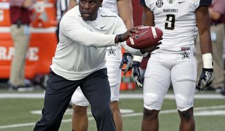 FILE - In this Sept. 1, 2016 file photo, Vanderbilt head coach Derek Mason leads players through a drill before an NCAA college football game against South Carolina, in Nashville, Tenn. Mason is 0-3 in season openers and said his lack of success kicking off the season is like a chip on his shoulder that stares at him every day, and it's something he hasn't let his players forget. (AP Photo/Mark Humphrey, File)