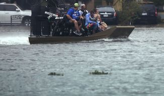 People are transported in an airboat during flooding from Tropical Storm Harvey in Orange, Texas, Wednesday, Aug. 30, 2017. (AP Photo/Gerald Herbert)