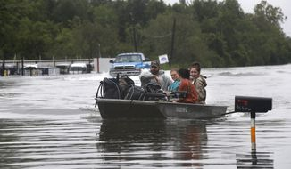 People navigate through floodwaters with their belongings during flooding from Tropical Storm Harvey in Orange, Texas, Wednesday, Aug. 30, 2017. (AP Photo/Gerald Herbert)