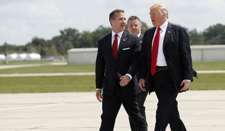 Missouri Gov. Eric Greitens, left, walks with President Donald Trump as they arrive in Springfield, Mo., Wednesday, Aug. 30, 2017. (AP Photo/Alex Brandon)