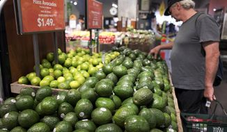 FILE - In this Monday, Aug. 28, 2017, file photo, a man shops for avocados at a Whole Foods Market, in New York. The splashy price cuts Amazon made as the new owner of Whole Foods attracted some curious customers. But whether shoppers who found cheaper alternatives to Whole Foods will come back, or those who never visited will give them a try, may help determine what kind of effect the deal has on how and where people do their grocery shopping. (AP Photo/Mark Lennihan, File)